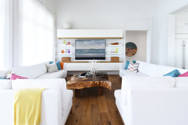 Modern home with living room, sectional, medium hardwood floor, coffee tables, and ceiling lighting. Great Room Photo 18 of Bahamas Style