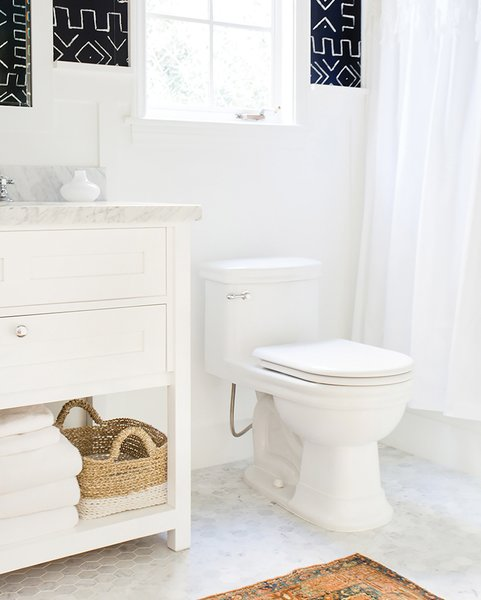 A basket stored discreetly near the toilet keeps extra toilet paper out of sight but easily accessible; Source: Casa Tres