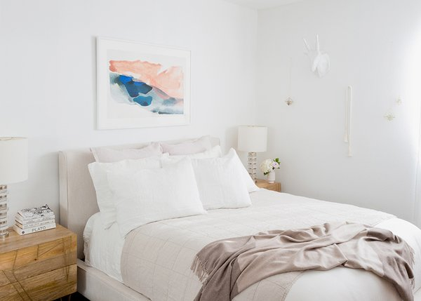 White Linen Bedding: Parachute. Oatmeal Essential Quilt: Parachute. Mushroom Striped Cashmere Throw: Parachute. Morning River Print: Minted. Dean Sand Queen Upholstered Panel Bed: Living Spaces. Roar + Rabbit Brass Geo Nightstands: West Elm. Clear Disc Table Lamps: West Elm; Source: Amy Bartlam/Parachute