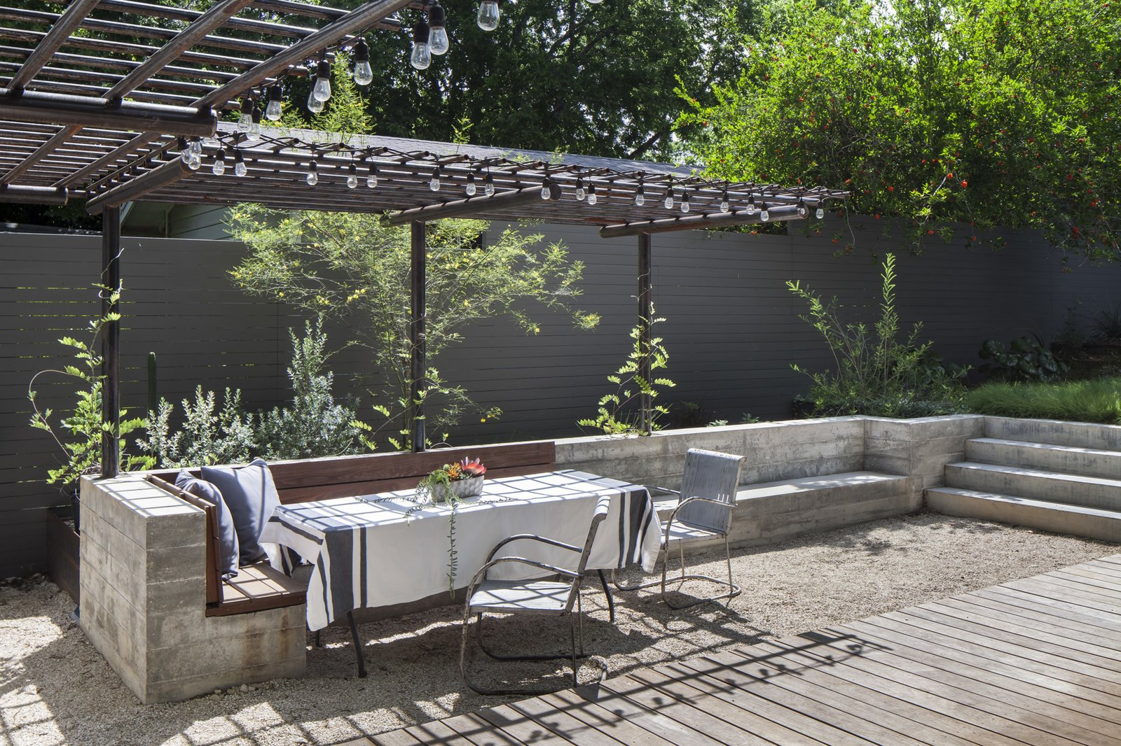 New outdoor dining space is defined and by a custom concrete and wood bench with steel trellis above .  Garner Pool & Casita by Elizabeth Baird