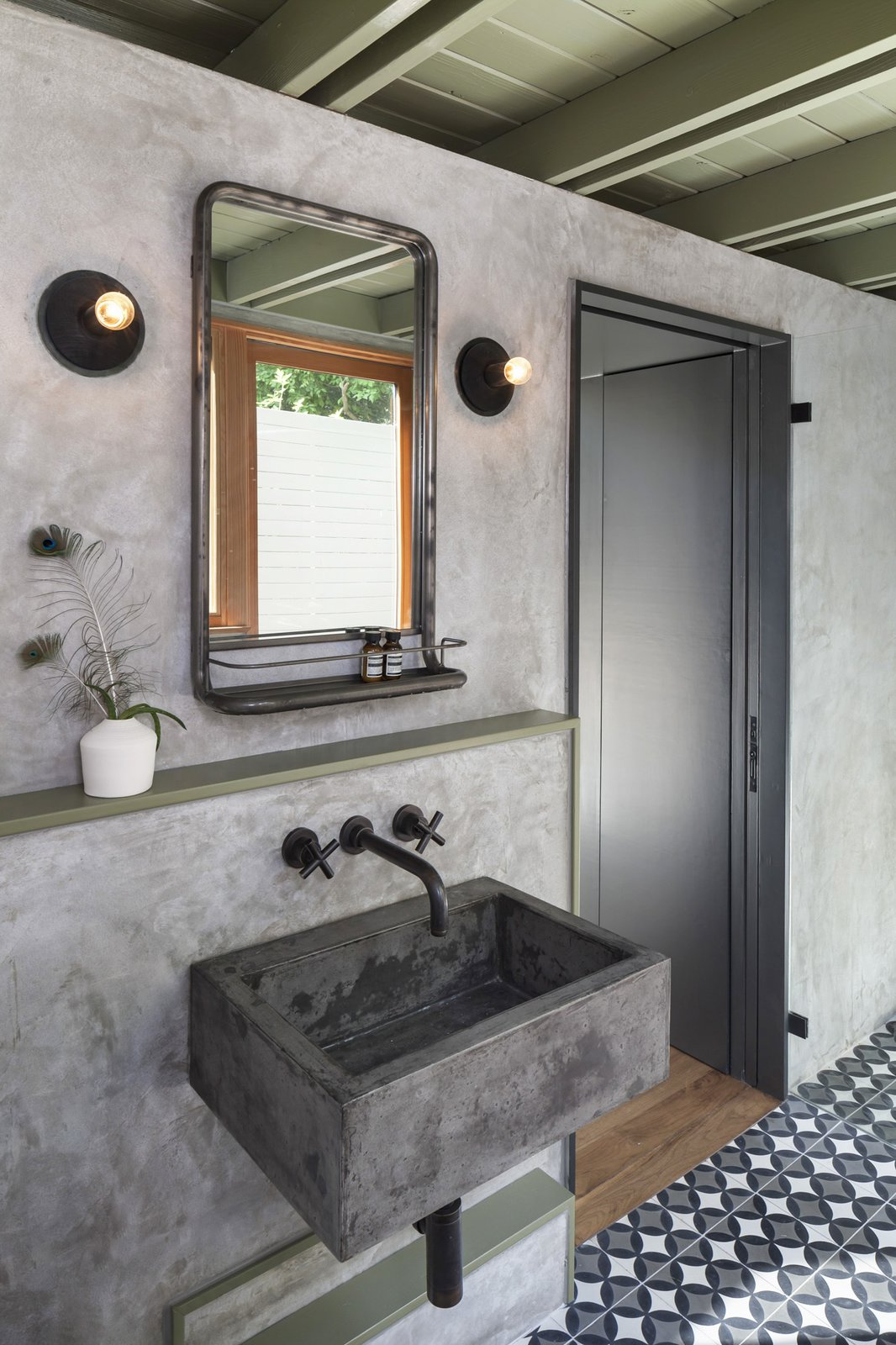 The new casita bathroom features a custom concrete sink, plaster walls, and custom concrete tile. Tagged: Bath Room, Wall Mount Sink, Wall Lighting, and Cement Tile Floor.  Garner Pool & Casita by Elizabeth Baird
