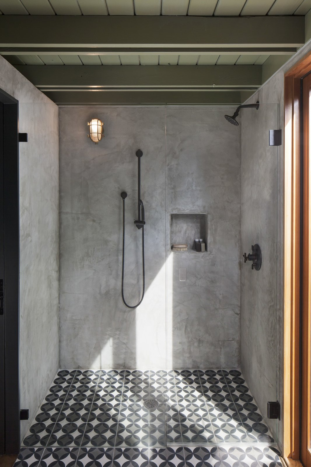 The concrete tile transitions into the plaster shower for a seamless look. Tagged: Bath Room, Cement Tile Floor, Wall Lighting, Full Shower, and Enclosed Shower.  Bathe by Jackie Antig from Garner Pool & Casita