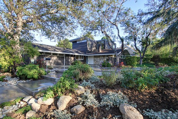 Modern home with front yard, wood fence, horizontal fence, outdoor, woodland, garden, rooftop, slope, vertical fence, trees, shrubs, hardscapes, gardens, boulders, and walkways. After_ street view looking south east Photo 2 of Alpine Street