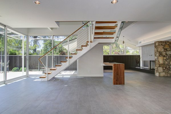 Modern home with wood fence, horizontal fence, sliding window type, metal, porcelain tile floor, console tables, corner fireplace, gas burning fireplace, recessed lighting, outdoor, and vertical fence. Living room- Entry & Den  Photo 6 of Alpine Street
