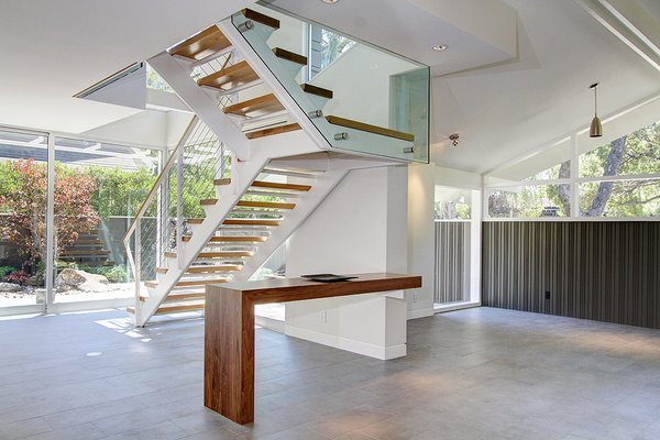 Modern home with wood fence, shrubs, garden, trees, woodland, hardscapes, boulders, walkways, small patio, porch, deck, hanging lighting, concrete patio, porch, deck, gardens, side yard, horizontal fence, metal, porcelain tile floor, sliding window type, console tables, cable railing, and wood railing. Stairway @ front entrance & Den Photo 7 of Alpine Street