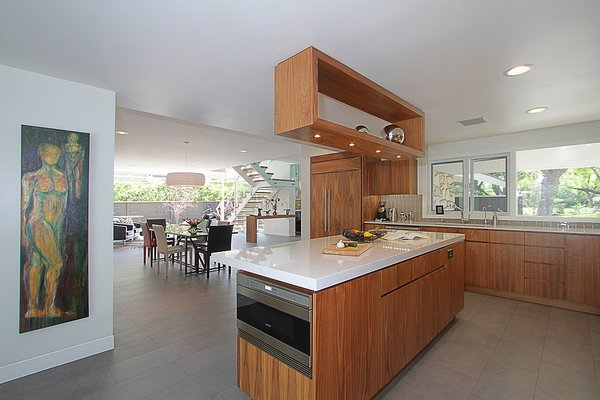 Modern home with kitchen, glass tile backsplashe, wood cabinet, porcelain tile floor, ceiling lighting, engineered quartz counter, recessed lighting, refrigerator, microwave, and undermount sink. Kitchen Dining and Living areas Photo 11 of Alpine Street