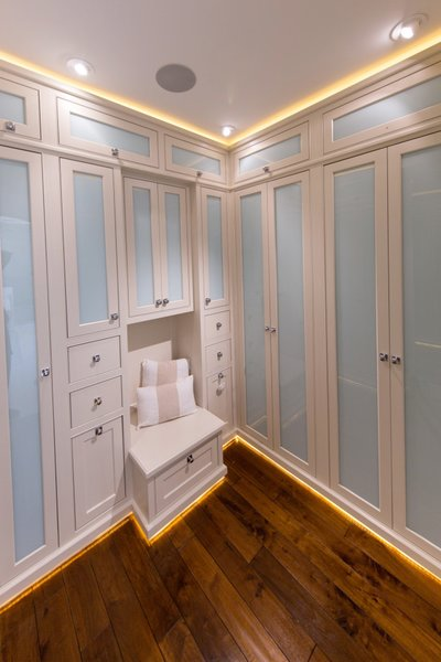 Master bedroom closet with custom cabinets, custom lighting features, and frosted glass panels to conceal the closet contents and keep everything dust free. Photo 4 of Modernized English Style modern home