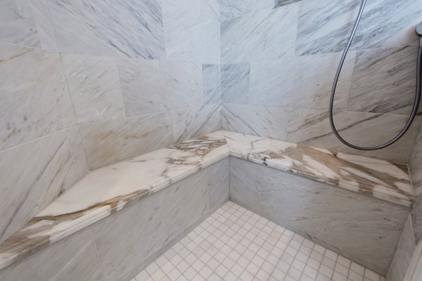 Book matched marble shower wall tiles and honed Calcutta marble seats to match the vanity countertops.  Photo 7 of Modernized English Style modern home