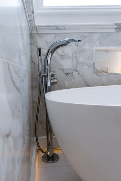 Polished chrome tub filler with wand and recessed baseboard lighting to give a romantic glow in the bathroom when the overhead lights are dimmed or off. Photo 10 of Modernized English Style modern home