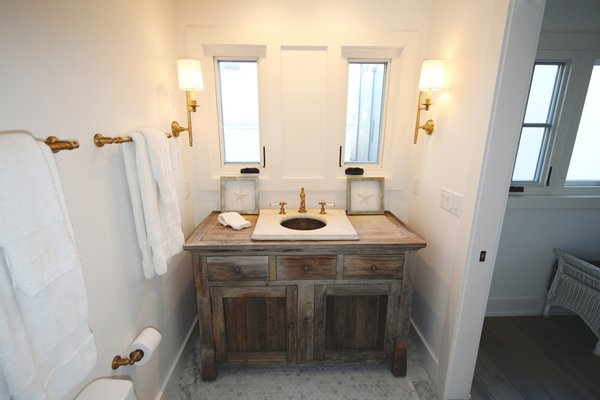 Vintage marble sink and brass lanterns complete this very special beach house getaway bathroom. Photo 3 of Streamlined Cape Cod at The Wedge modern home