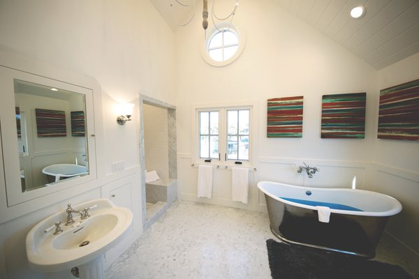 Master bathroom with vaulted ceiling and imported stainless tub create the ultimate bathing experience.  Photo 4 of Streamlined Cape Cod at The Wedge modern home