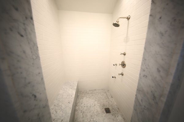 1920s inspired walk in shower with marble trim and seats.  Photo 5 of Streamlined Cape Cod at The Wedge modern home
