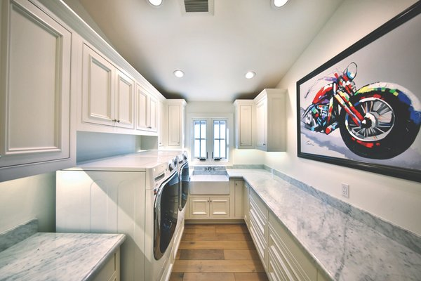 Laundry room with extra counter space and storage to service needs of large family spending time at the beach. Photo 6 of Streamlined Cape Cod at The Wedge modern home