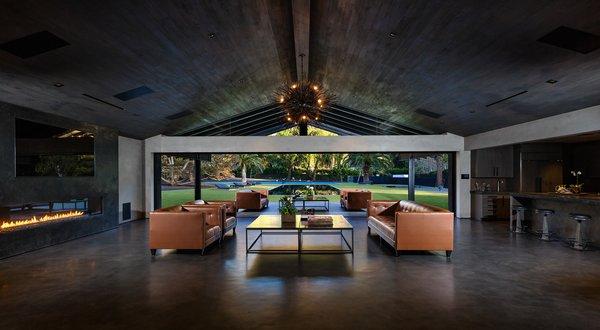 Living room opens to reveal spacious backyard. Photo  of Malibu Lake House modern home