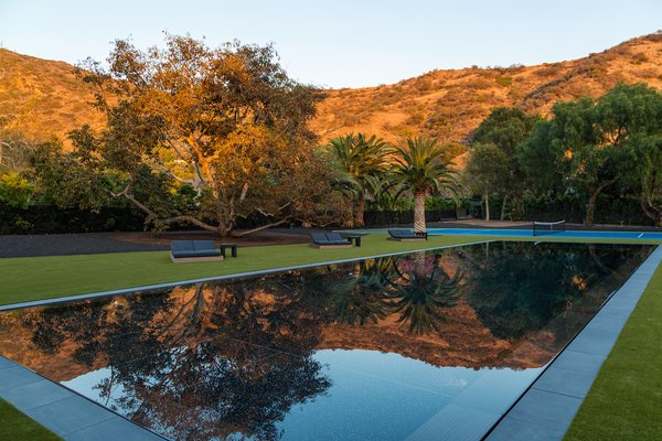 Infinity pool, green grass and tennis court in the backyard. Photo 4 of Malibu Lake House modern home