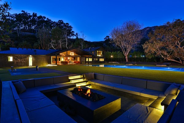Backyard with infinity pool, seating and fire pit. Photo 9 of Malibu Lake House modern home