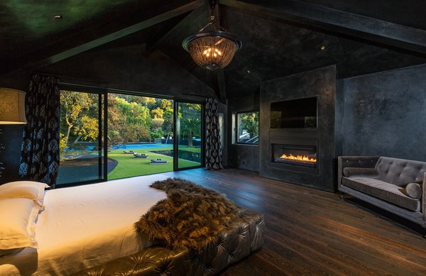 Master bedroom with fireplace. Photo 10 of Malibu Lake House modern home