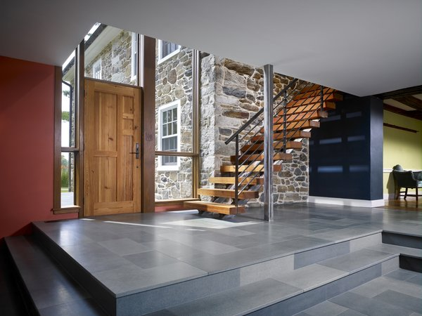 Modern home with exterior, wood, swing door type, picture window type, wood railing, wood tread, and staircase. Reclaimed wood treads are used in a minimally detailed open stair connecting living spaces to a new hall and bedrooms above. Photo 7 of Modern Farmhouse Addition