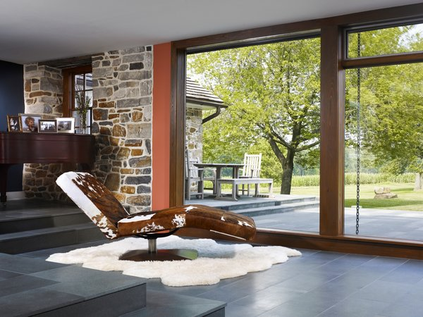 Modern home with large patio, porch, deck, stone patio, porch, deck, pavers patio, porch, deck, picture window type, recliner, stone tread, chair, and living room. The addition connects living spaces to the idyllic landscape. Photo 8 of Modern Farmhouse Addition