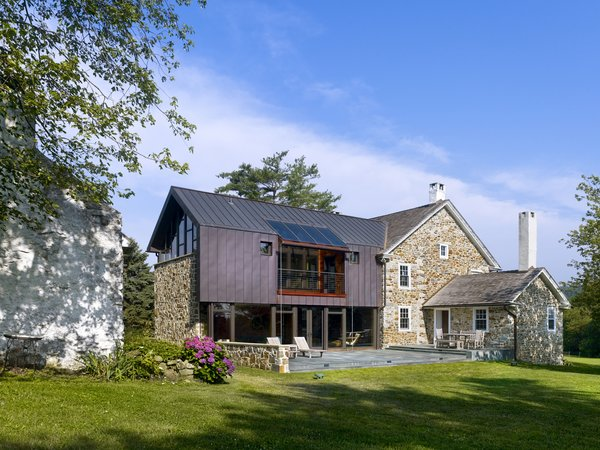 Modern home with field, back yard, vegetables, hardscapes, stone patio, porch, deck, grass, trees, large patio, porch, deck, pavers patio, porch, deck, outdoor, and landscape lighting. A new stone patio connects living spaces to the rural site beyond. Photo 2 of Modern Farmhouse Addition