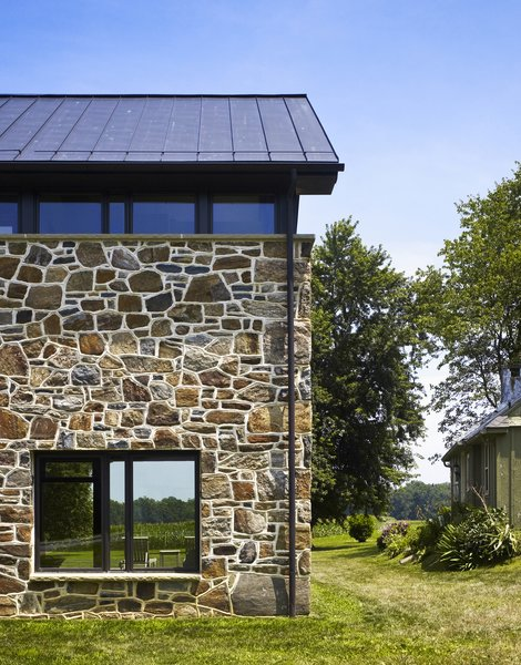 Modern home with flowers, trees, front yard, shrubs, picture window type, metal, casement window type, wood, and outdoor. The addition acts as a threshold from a new entry to the site beyond. Photo 4 of Modern Farmhouse Addition
