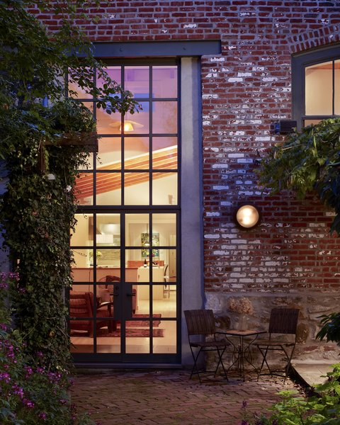 Modern home with trees, back yard, flowers, shrubs, large patio, porch, deck, hardscapes, gardens, walkways, exterior, metal, swing door type, windows, and picture window type. A  steel window system infills the garden wall's existing masonry opening. Photo 9 of Garden House