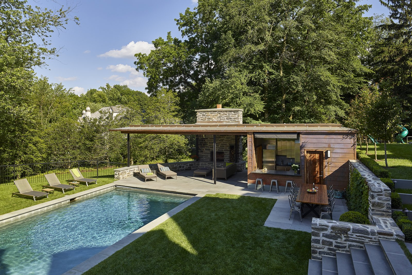 The pool house was designed to negotiate the terraced site. Tagged: Slope, Stone Patio, Porch, Deck, Trees, Hardscapes, Walkways, Outdoor, Large Pools, Tubs, Shower, Back Yard, Swimming Pools, Tubs, Shower, Standard Construction Pools, Tubs, Shower, and Vertical Fences, Wall.  Modern Pool House for Sloped Site by Wyant Architecture