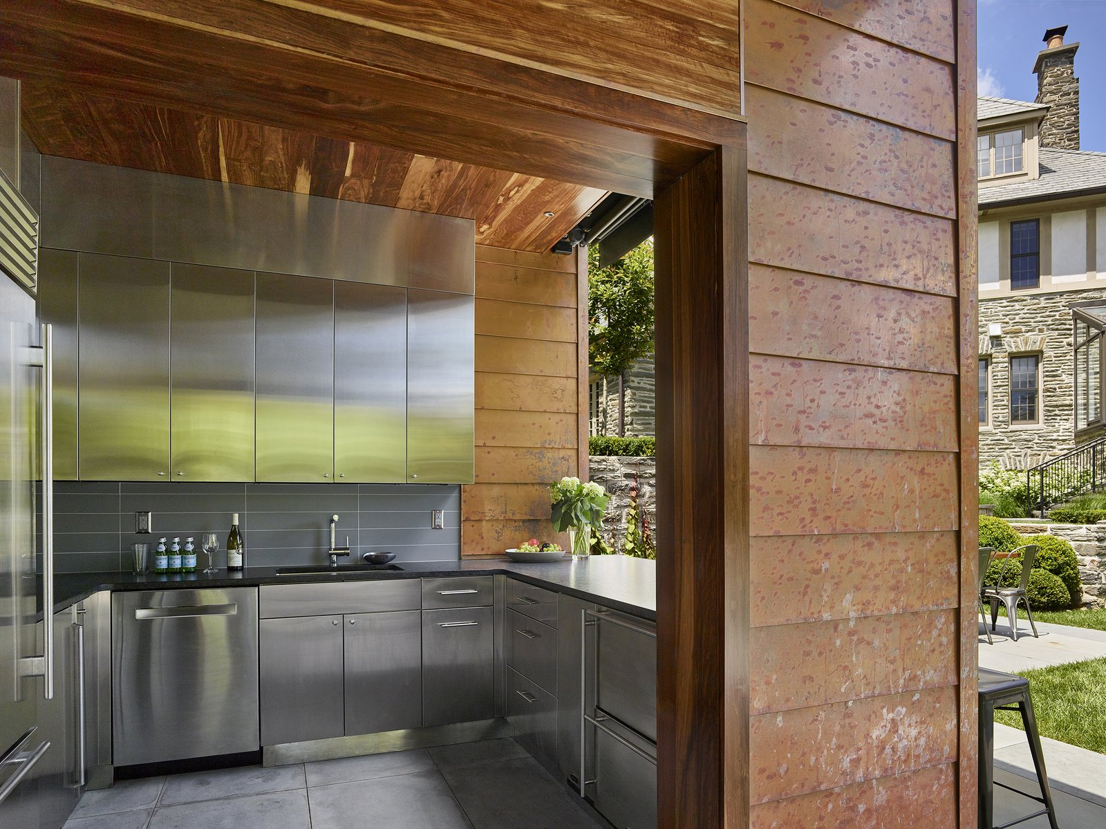 Outdoor kitchen Tagged: Slope, Trees, Walkways, Hardscapes, Stone, Back Yard, Shrubs, Pavers, Vertical, Granite, Dishwasher, Metal, Limestone, Refrigerator, Ceramic Tile, Beverage Center, Ice Maker, Undermount, and Kitchen.  Best Kitchen Stone Photos from Modern Pool House for Sloped Site