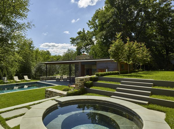 Modern home with trees, back yard, walkways, stone patio, porch, deck, shrubs, slope, hardscapes, pavers patio, porch, deck, vertical fence, outdoor, large pool, small pool, plunge pool, swimming pool, and standard construction pool. Stone terrace steps and hot tub. Photo 5 of Pool House for Sloped Site