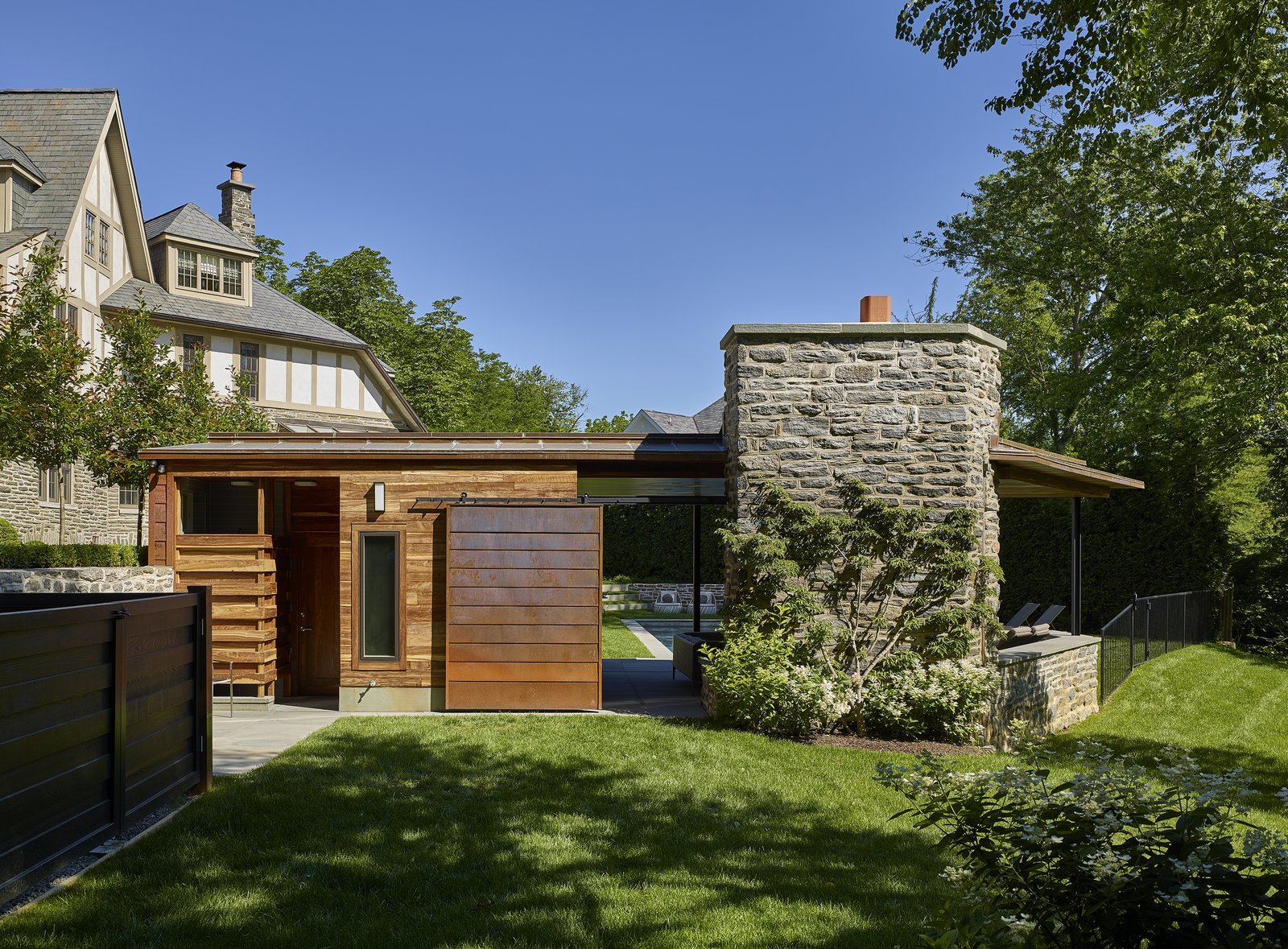 Entry to private spaces at rear of pool house. Tagged: Slope, Trees, Walkways, Hardscapes, Back Yard, Shrubs, Vertical, Standard Layout, Wood Burning, Metal, Exterior, Sliding, and Outdoor.  Best Outdoor Hardscapes Slope Photos from Modern Pool House for Sloped Site