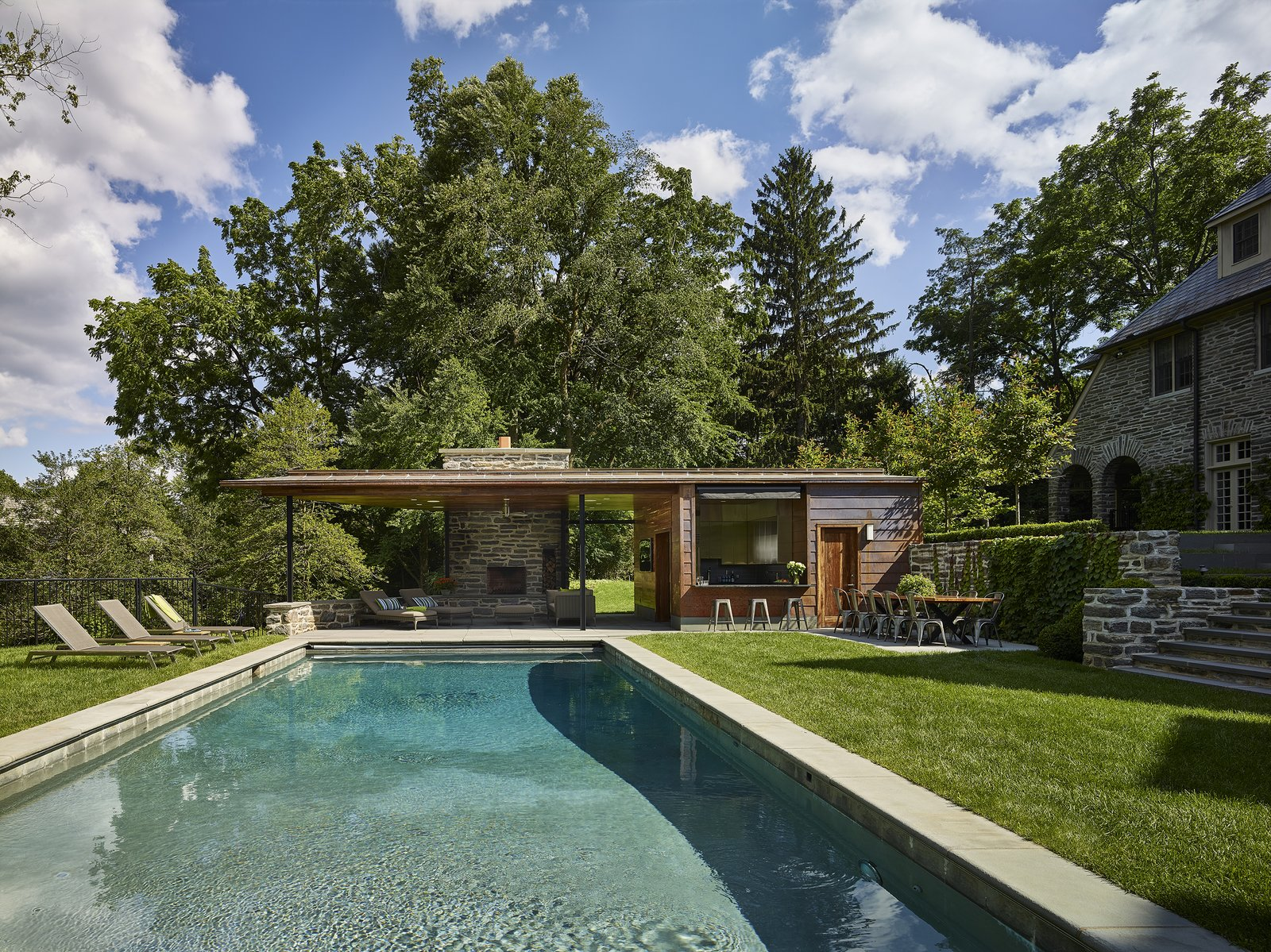 View from pool Tagged: Standard Layout Fireplace, Wood Burning Fireplace, Recliner, Limestone Floor, Back Yard, Trees, Shrubs, Table, Chair, and Outdoor.  Modern Pool House for Sloped Site by Wyant Architecture