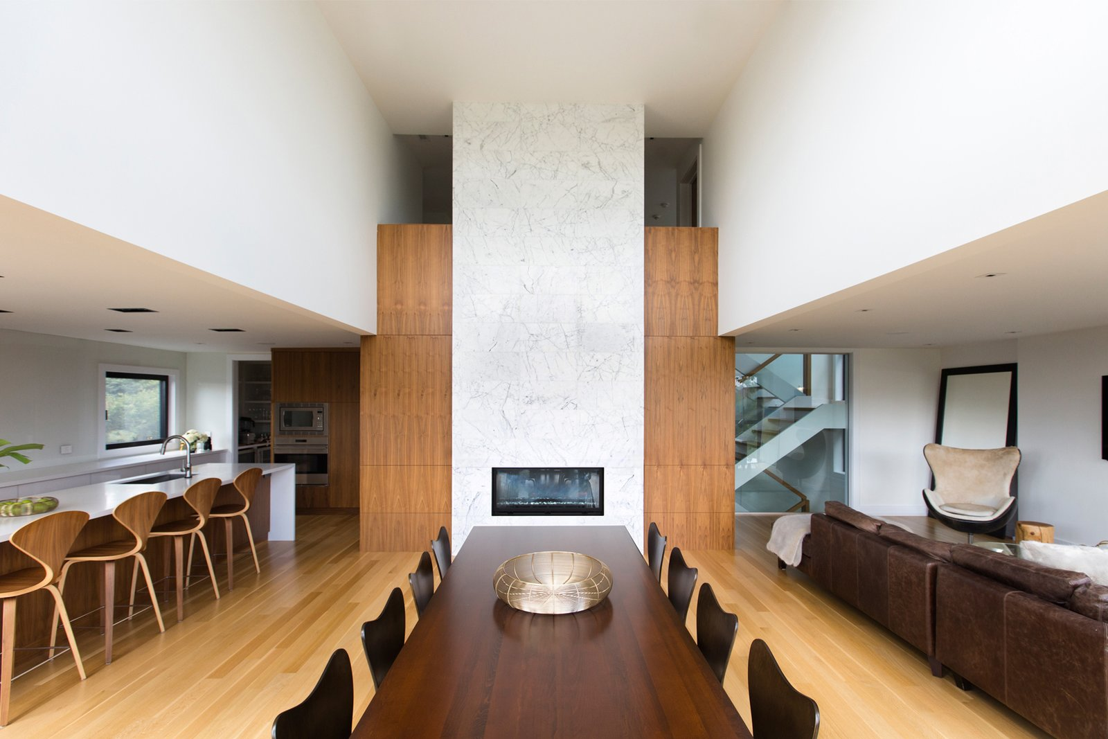A central, double height, dual-sided fireplace anchors the home, connecting the main living spaces with the entrance and spacious gallery foyer on the opposite side.  Ravine House by FrankFranco Architects