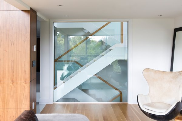 Beyond the custom glass wall in the family room is an open riser oak staircase, with glass guards and a wood handrail. Photo 8 of Ravine House modern home