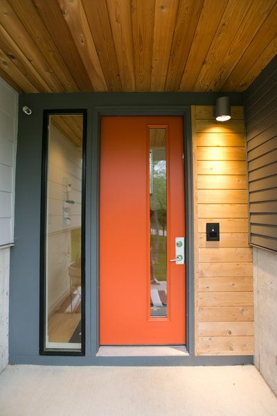 Mod-century modern inspired front door in a pop of orange against a two-toned grey exterior Photo 3 of The Sangar House modern home
