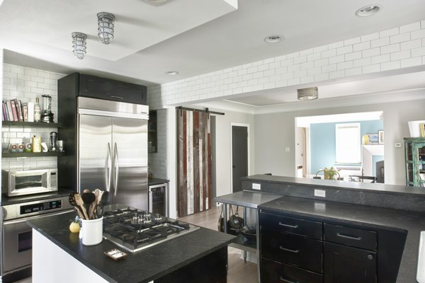 Modern home with kitchen, granite counter, subway tile backsplashe, wood cabinet, ceiling lighting, medium hardwood floor, refrigerator, and beverage center. Kitchen and Dining Area Photo 3 of Bigelow Residence