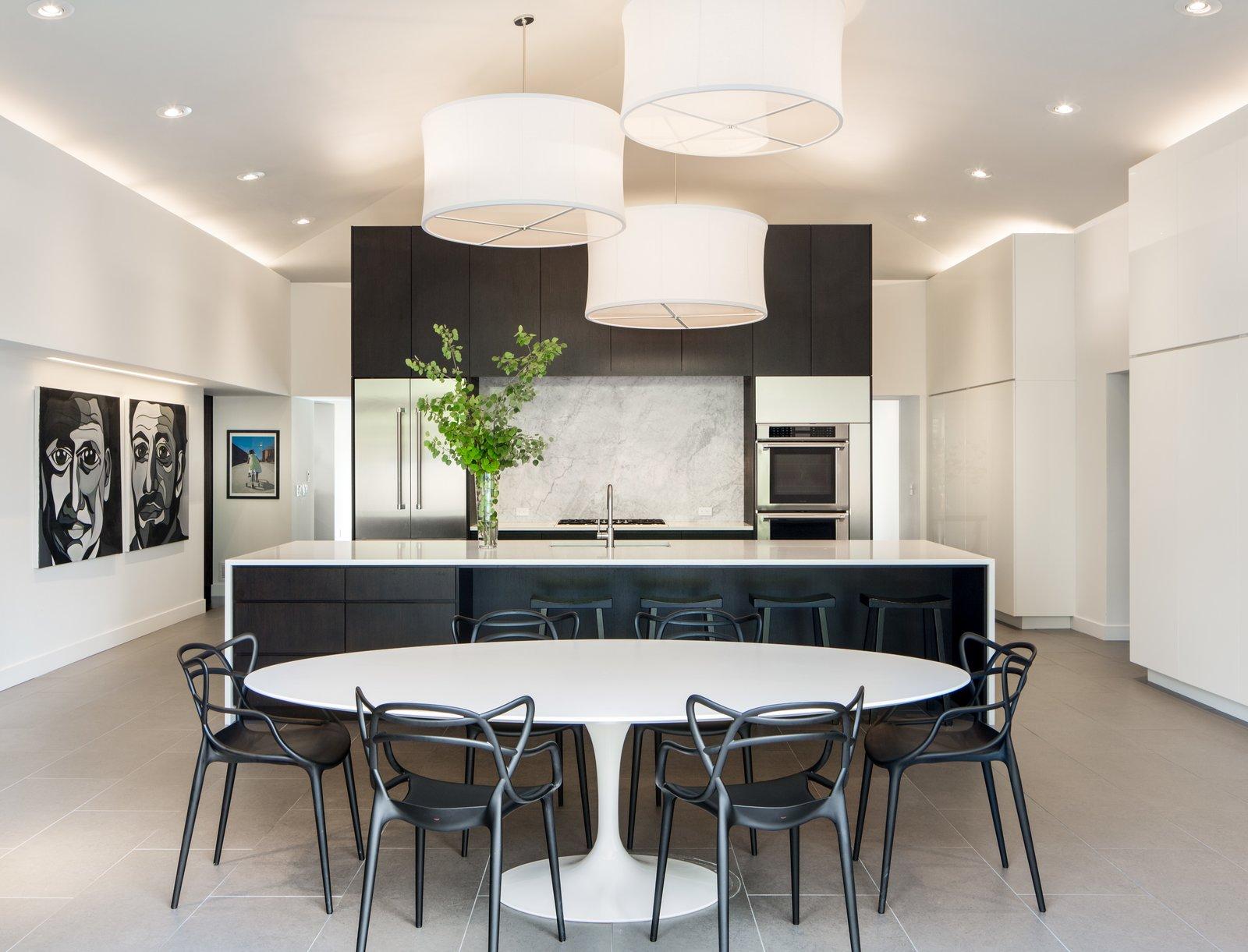 Kitchen and Dining Area  Tagged: Kitchen, Engineered Quartz, Dark Hardwood, Wood, Stone Slab, Pendant, Wall Oven, Refrigerator, and Undermount.  Best Kitchen Wall Oven Dark Hardwood Photos from Donner Residence