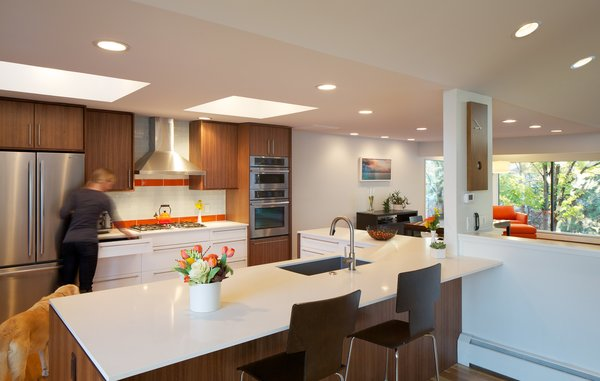 Modern home with kitchen, engineered quartz counter, wood cabinet, medium hardwood floor, ceramic tile backsplashe, ceiling lighting, refrigerator, wall oven, cooktops, and undermount sink. Kitchen with custom walnut cabinets by AvenueTwo. Caesarstone Countertops Photo 3 of Hornstein Residence