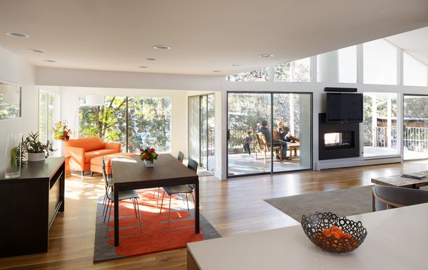 Modern home with dining room, table, ceiling lighting, chair, medium hardwood floor, and two-sided fireplace. Living and Dining Area Photo 5 of Hornstein Residence