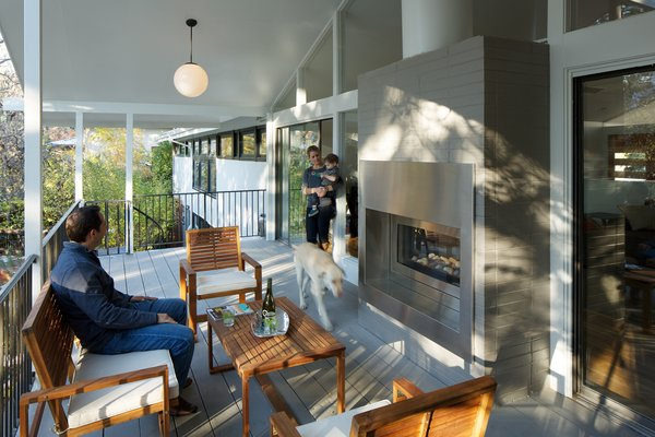 Modern home with dining room, bench, table, medium hardwood floor, pendant lighting, chair, and two-sided fireplace. Deck and See Thru Fireplace Photo 7 of Hornstein Residence
