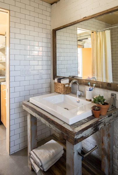 Modern home with bath room, wood counter, vessel sink, subway tile wall, and concrete floor. Bathroom Vanity. Salvaged from Blacksmith workshop bench. Original window frame used for mirror. Subway tile interior.  Photo 10 of Blacksmith Shop