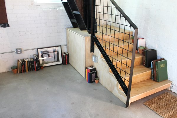 Modern home with living room, bookcase, and concrete floor. Plywood Stair Landing with Storage Below Photo 4 of Blacksmith Shop