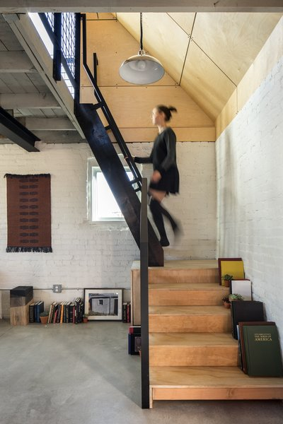 Modern home with staircase, wood tread, and metal railing. Stairs to Bedroom. Original exposed interior brick. Ships ladder to loft/bedroom. Original loft floor/ceiling. Polished concrete floor below.  Photo 12 of Blacksmith Shop