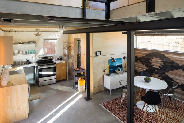 Modern home with living room, ceiling lighting, chair, and concrete floor. Living and Kitchen Area from Staircase Photo 13 of Blacksmith Shop