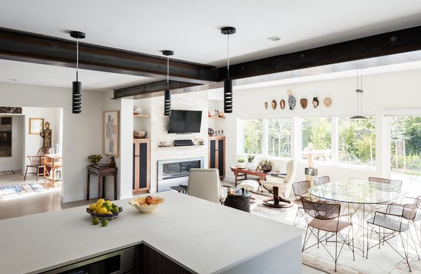 Modern home with living room, chair, ceiling lighting, light hardwood floor, and gas burning fireplace. Kitchen with Dining and Living Beyond Photo 6 of Artist Residence