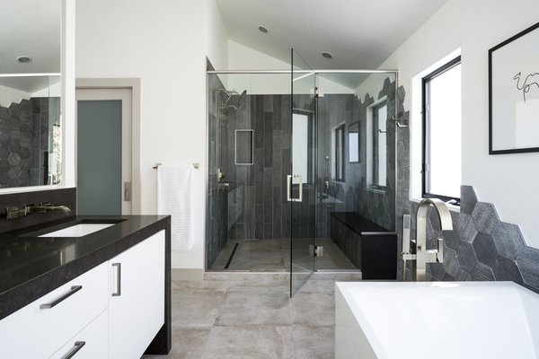 Master bathroom suite. Gloss white vanity with dark quartz waterfall countertop. Hexagon tile drops down wall from shower enclosure to tub surround.