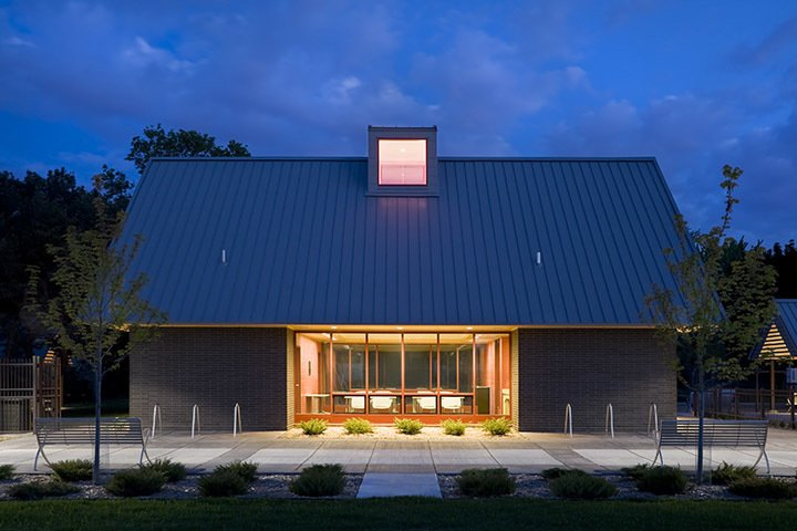 Elevation of the brick park building at dusk.  A modern and fresh approach to a small public park in Minnesota. by U+B