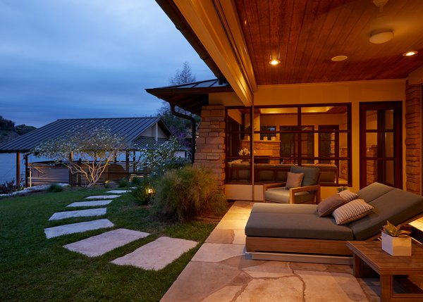 Modern home with outdoor, back yard, shrubs, stone patio, porch, deck, trees, hardscapes, and walkways. Back patio feature Restoration Hardware's Costa Luxe collection with view of boat dock and peak into the screened porch Photo  of Lake Austin Remodel