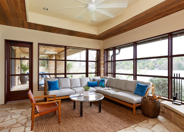 Screened porch with custom abaca rug, vintage leather sling chair, client's own quartz coffee table and custom sectional with Perennials and Holland and Sherry fabrics.