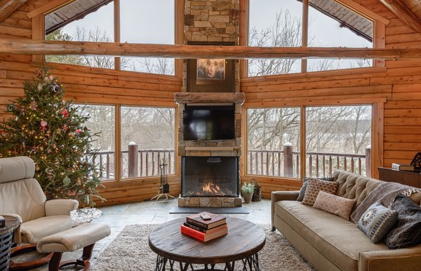 """Modern home with living room and gas burning fireplace. This install was done by All Seasons Fireplace in Minnesota: """"The homeowners loved the original wood burning fireplace, but their contractor suggested that cutting and carrying wood on a daily basis would get old fast, even with four boys at home to help. They wanted to maintain the large viewing area that the wood burning fireplace allowed, so this Trisore 100H gas fireplace model from European Home was the perfect choice for the room."""" Photo  of Northwoods Log Cabin"""
