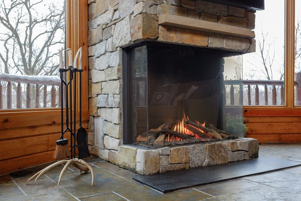 Modern home with living room and gas burning fireplace. The height of the Trisore 100H gives you a great view of the flames on the warm, glowing log set. Photo 5 of Northwoods Log Cabin
